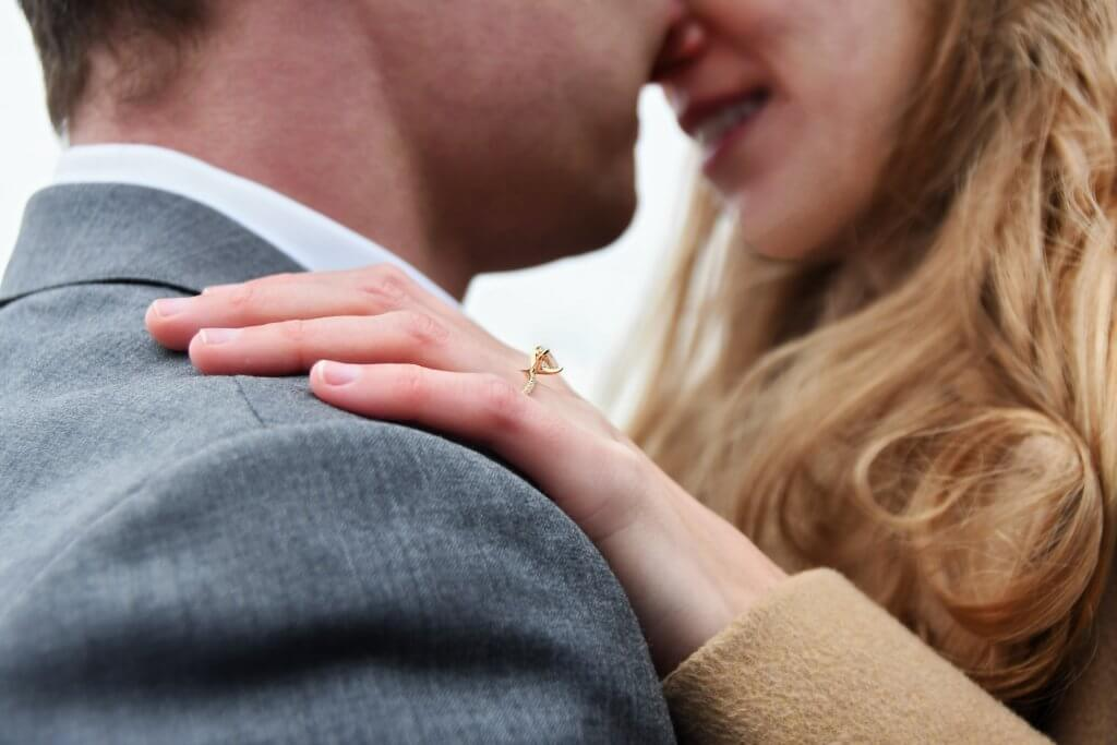 man-hugging-woman-with-a-solitaire-cut-diamond-engagement-ring-The-Diamond-Solitaire-Setting-2-1