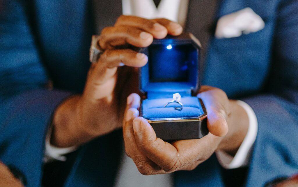man holding round engagement ring - Diamond Clarity I1 and I2